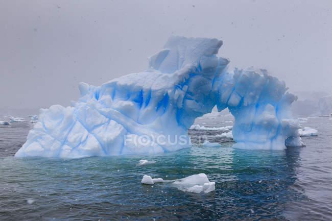 Blaue Eisberg Bogen in Schneewetter, Paradise Bay, Graham-Land, antarktische Halbinsel, Antarktis, Polarregionen — Stockfoto