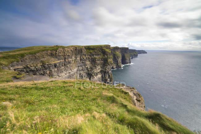 Скалы Мохер с пасмурным небом, край региона Буррен в графстве Клэр, Мюнстер, Ирландия — стоковое фото