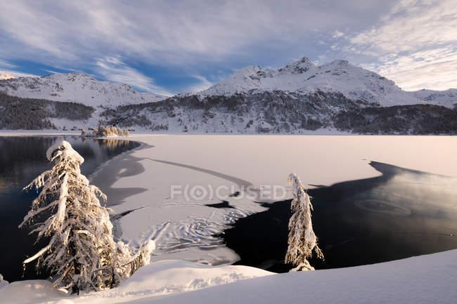 Frozen Lake Sils with snow covered mountains on background, Plaun da Lej, Maloja Region, Canton of Graubunden, Engadine, Switzerland — Stock Photo