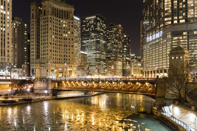 Torre Trump iluminada y congelado río de Chicago en la noche, Chicago, Illinois, Estados Unidos de América, Norte América - foto de stock