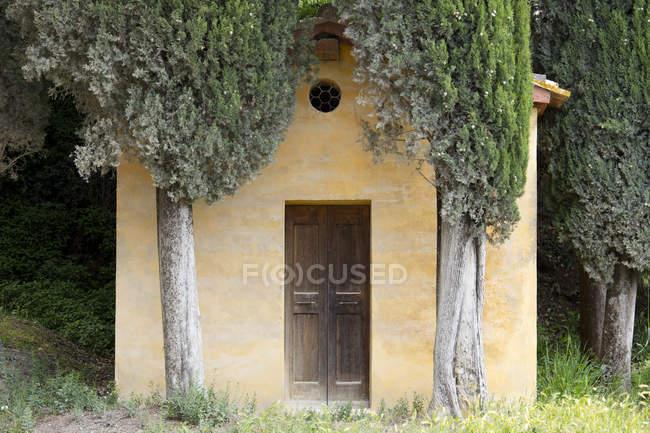 Piccola Cappella Toscana, circondata da alberi di cipresso — Foto stock