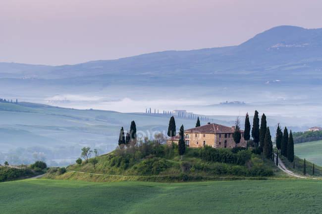 Podere Belvedere und nebligen Hügeln bei Sonnenaufgang, Toskana, Italien — Stockfoto