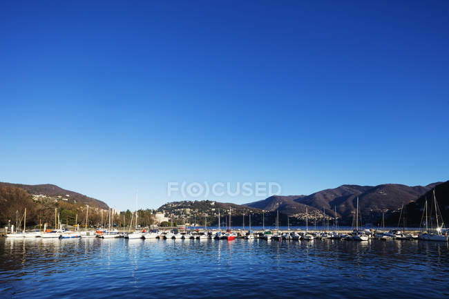 Lake Como and moored boats in mountains under bright blue sky, Lombardy, Italian Lakes, Italy — Stock Photo