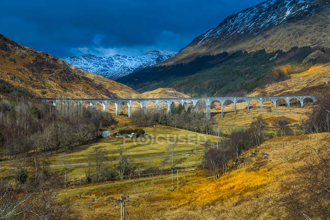 The Glenfinnan Viaduct in mountains under stormy sky on the West Highland Line in Glenfinnan, Inverness-shire, Scotland, United Kingdom — Stock Photo