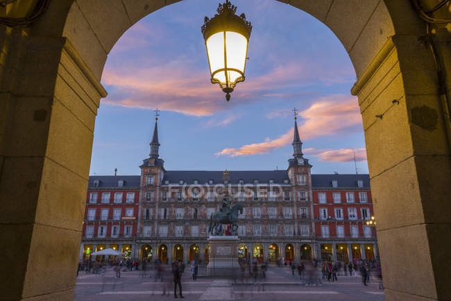 Casa de la panadería en la Plaza Mayor por el arco al atardecer, Madrid, España - foto de stock