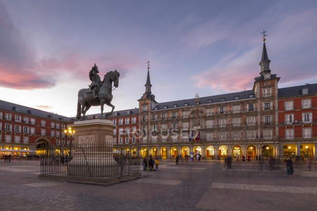 Estatua de Felipe III y la arquitectura iluminada en la Calle Mayor al atardecer, Madrid, España - foto de stock