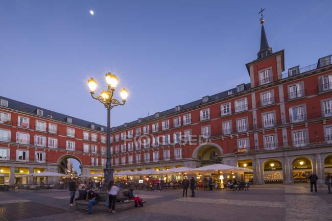 Restaurantes iluminados en la Plaza Mayor al atardecer, Madrid, España - foto de stock