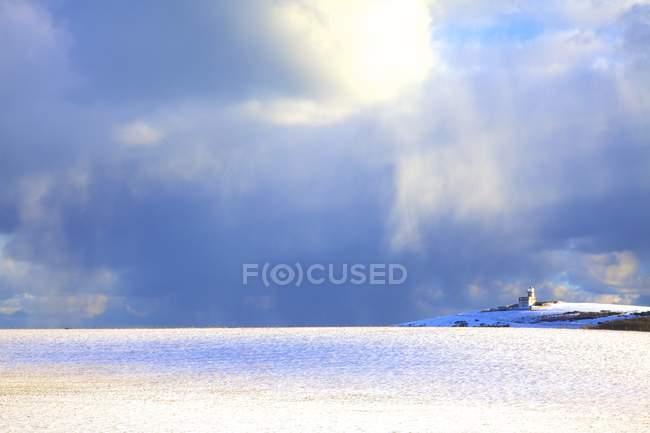 Bewölkter Himmel mit Sonnenschein über verschneite Landschaft und Belle Tout Leuchtturm im Hintergrund, Beachy Head South Downs, East Sussex, England, Vereinigtes Königreich — Stockfoto