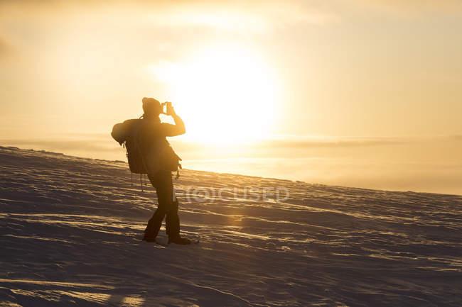 Hiker taking photo of bright sunset, Pallas-Yllastunturi National Park, Muonio, Lapland, Finland, Europe — Stock Photo