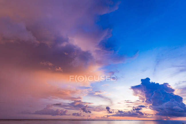 Cloudy pink dramatic sky over sea at sunset — Stock Photo