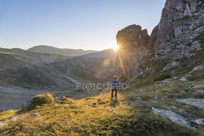 Sun rays disappearing behind a rock face and man standing in Rila Mountains, Bulgaria — Stock Photo