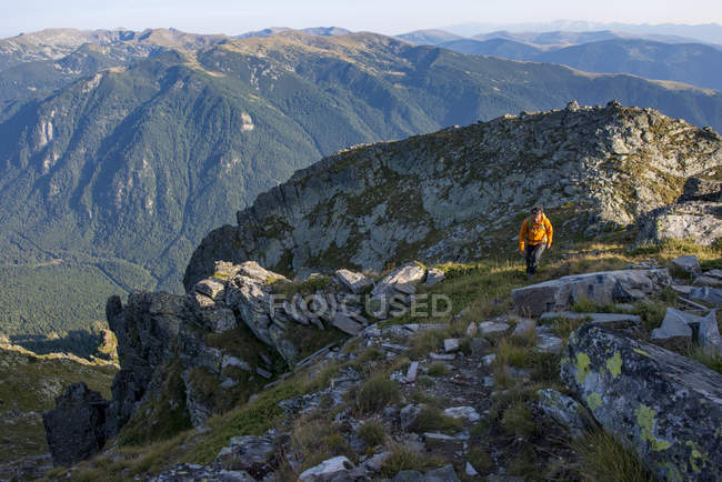 Hiker climbing along a high ridge near Maliovitsa in the Rila Mountains with views of valleys and hills, Bulgaria — Stock Photo