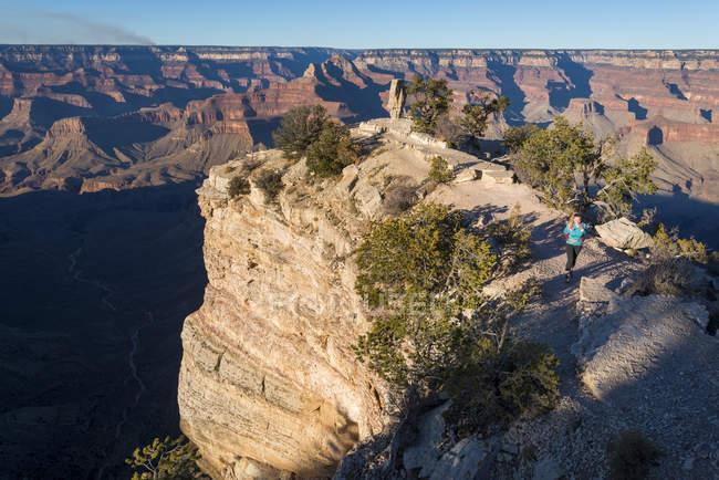 Pôr do sol sobre o Grand Canyon e feminina turista olhando a vista, Arizona, Estados Unidos da América, da América do Norte — Fotografia de Stock