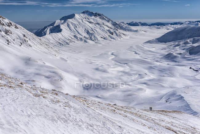 Заснеженный Скалистых гор и плато с туристов на фоне, Кампо Imperatore, Абруццо, Апеннины, Италия — стоковое фото