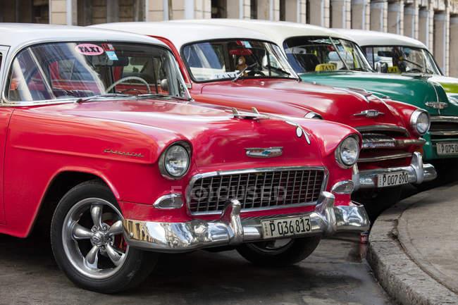 Красный и зеленый старинные американские автомобили, припаркованные в такси, Гавана, Куба, Вест-Индии, Карибский — стоковое фото