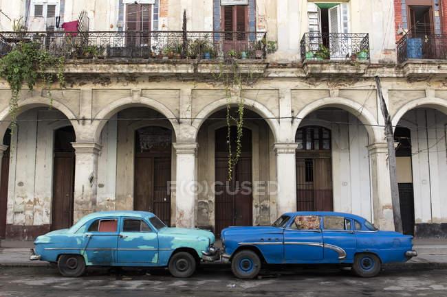 Синий автомобили перед ветхие здания — стоковое фото