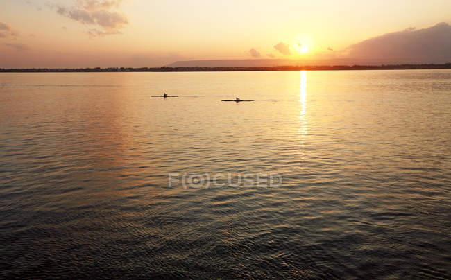 Piragüistas flotando en el mar en el atardecer, Ortigia, Sicilia, Italia, Mediterráneo, Europa - foto de stock