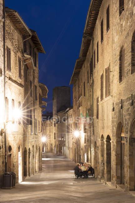 Rua estreita iluminada em San Gimignano na noite, Toscana, Itália, Europa — Fotografia de Stock