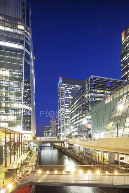 Modernos edificios iluminados en el distrito de Canary Wharf en la noche, Docklands, Londres, Inglaterra, Reino Unido - foto de stock