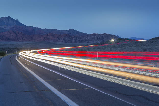 Trail lights on road in mountains at dusk in Red Rock Canyon National Recreation Area, Las Vegas, Nevada, United States of America, North America — Stock Photo