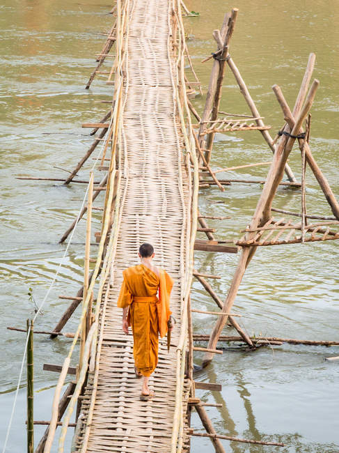 Orange-clad Buddhist monk crossing a bamboo bridge, Luang Prabang, Laos, Indochina, Southeast Asia, Asia — Stock Photo
