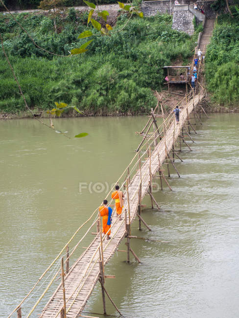 Orange-clad Buddhist monks crossing a bamboo bridge, Luang Prabang, Laos, Indochina, Southeast Asia, Asia — Stock Photo