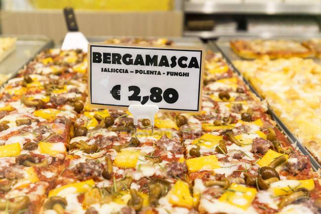 In Scheiben geschnittene Pizza in Bäckerei mit Preisschild — Stockfoto