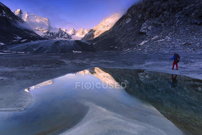 Hiker looking at sunrise from a pond at Forno Glacier, Forno Valley, Maloja Pass, Engadine, Graubunden, Switzerland — Stock Photo