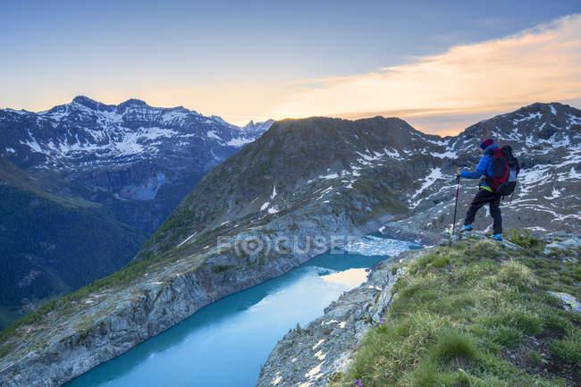Молодой турист смотрит на озеро Пирола сверху на восходе солнца, долина Кьяреджио, Вальмаленко, Вальтеллина, Ломбардия, Италия, Европа — стоковое фото