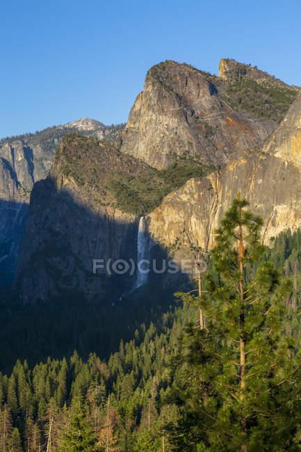 Valle de Yosemite con montañas rocosas y Bridalveil Fall, Parque Nacional de Yosemite, California, Estados Unidos, Norteamérica - foto de stock