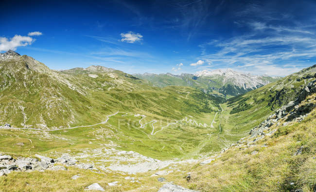 Panoramic of winding road and green valley towards the village of Splugen, Spluga Pass, canton of Graubunden, Switzerland — Stock Photo
