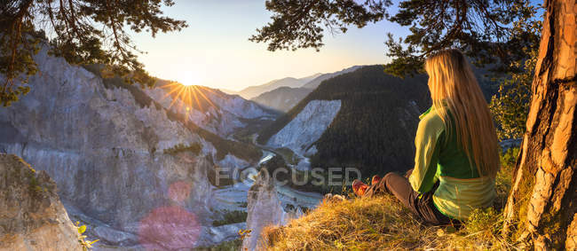 Female tourist sitting and looking at mountains at sunset, Rhine Gorge, Flims, District of Imboden, Canton of Grisons (Graubunden), Switzerland, Europe — Stock Photo