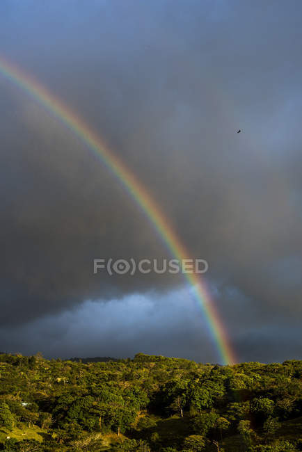 Rainbow in cloudy sky over Monteverde Cloud Forest Reserve at sunset, Puntarenas, Costa Rica, Central America — Stock Photo