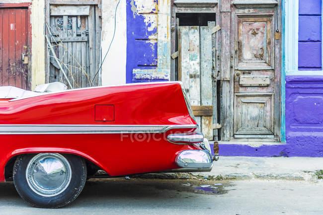 Красный винтажный автомобиль припаркован против красочные старое здание в Гаване, Куба, Вест-Индии, Карибского бассейна, Центральной Америки — стоковое фото