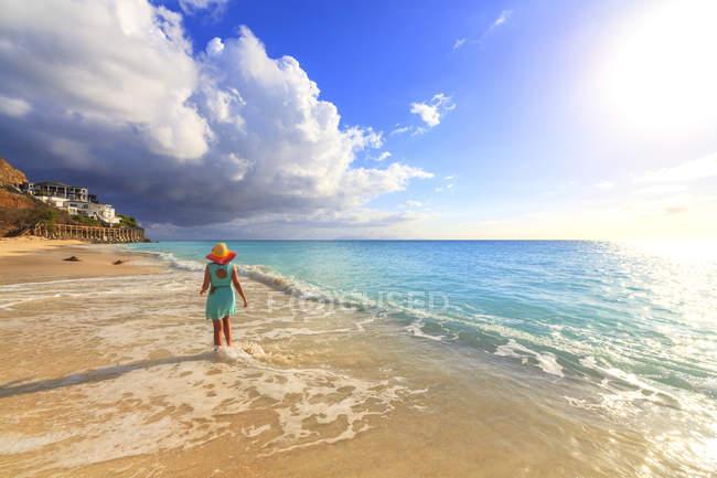 Rückansicht der Frau im Hut zu Fuß auf Ffryes Beach, Antigua, Antigua und Barbuda, Leeward Islands, Westindien, Karibik, Mittelamerika — Stockfoto