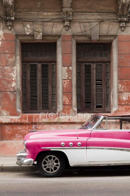 Frente de blanca y Rosa viejo coche vintage frente fachada cutre, la Habana, Cuba, Antillas, Caribe, América Central - foto de stock