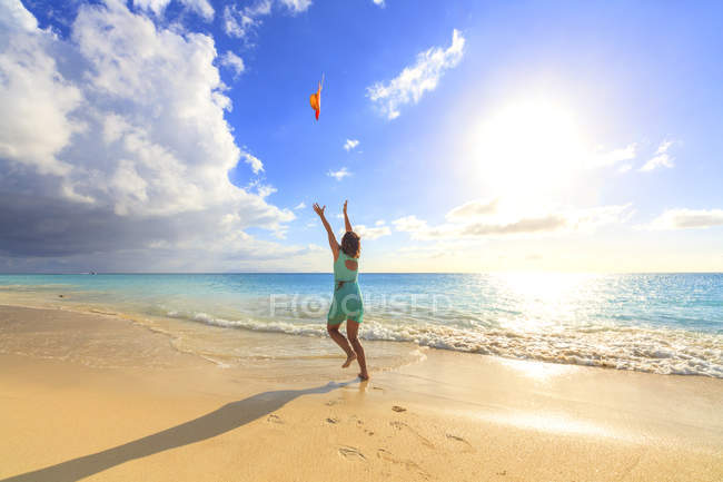 Donna in mare lanciando cappello in aria, Ffryes Beach, Antigua, Antigua e Barbuda, Isole Sottovento, Indie Occidentali, Caraibi, America Centrale — Foto stock