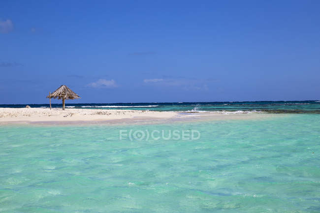 Crystal clear water and sandy beach with straw umbrella, Mopian, The Grenadines, West Indies, Caribbean, Central America — Stock Photo
