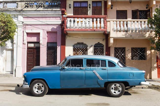 Старый синий американский автомобиль припаркован напротив старого здания, Сьенфуэгос, Куба, Вест-Индии, Карибский бассейн, Центральная Америка — стоковое фото