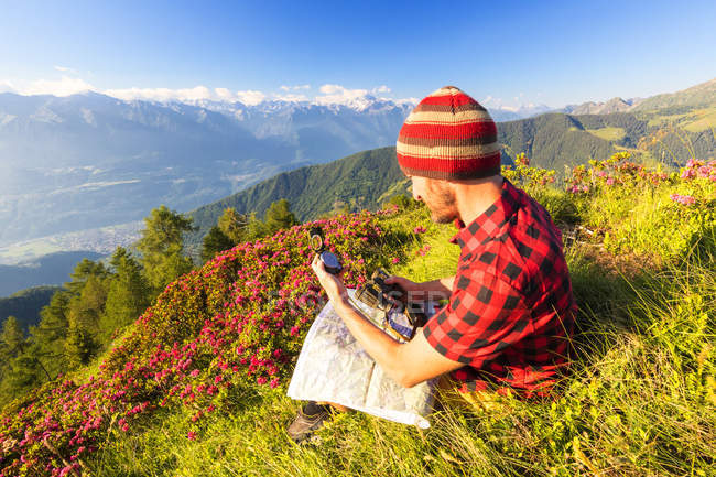 Hiker with map and binoculars sitting and looking at view in Rhaetian Alps , Bitto Valley, Lombardy, Italy — Stock Photo