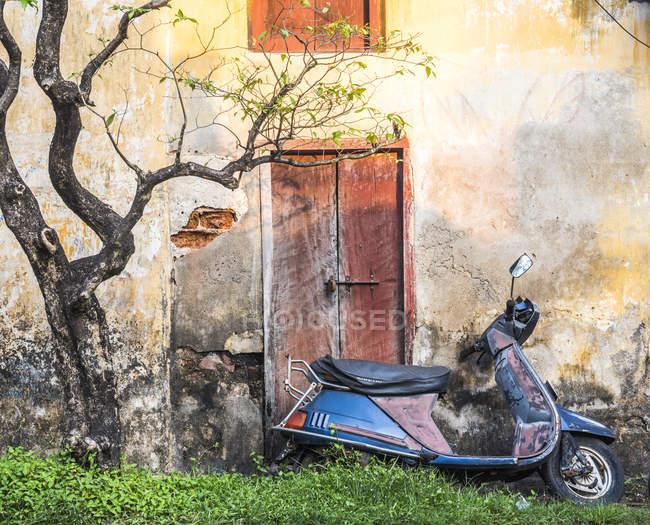 Altes Motorrad lehnt sich an schäbiges Gebäude — Stockfoto