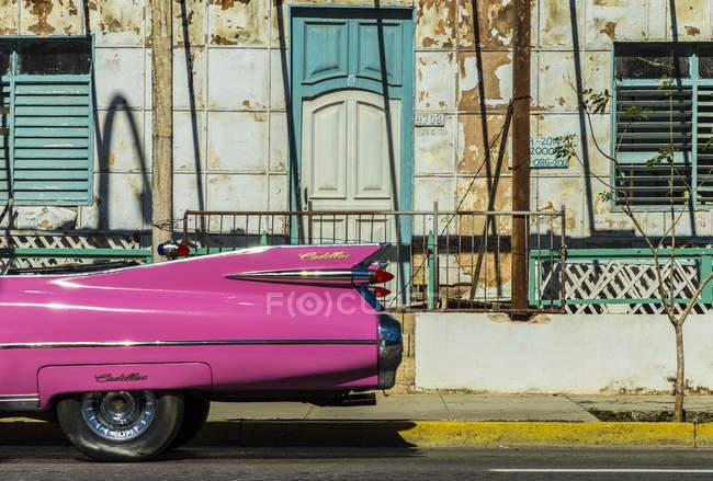 Ретро классические розовый американский автомобиль, проезжающих мимо старого здания в Варадеро, Куба, Вест-Индии, Карибский бассейн, Центральная Америка — стоковое фото