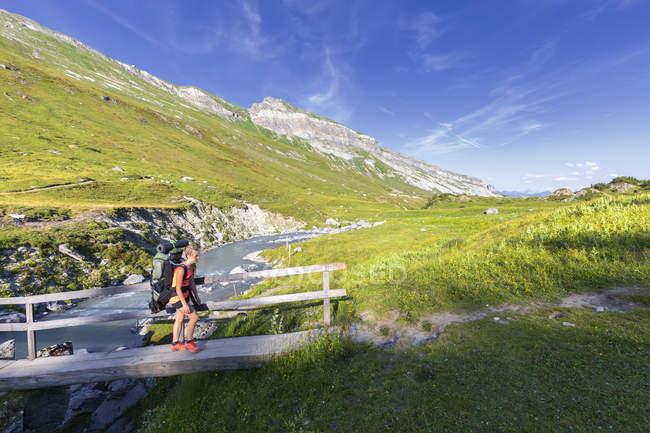 Randonneur féminin avec sac à dos marchant à travers une passerelle, Unterer Segnesboden, Flims, district d'Imboden, canton des Grisons (Graubunden), Suisse — Photo de stock
