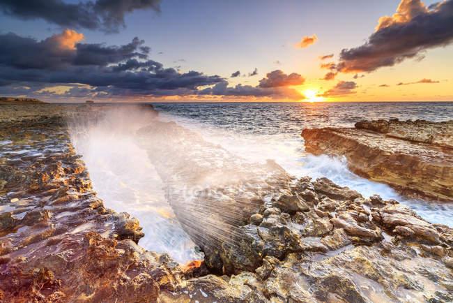 Wellen, die auf Klippen am Sonnenaufgang, Teufelsbrücke, Antigua, Antigua und Barbuda, Leeward Islands, West Indies, Karibik, Mittelamerika — Stockfoto