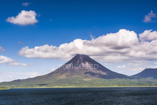 Vulcão Arenal atrás de Laguna de Arenal (lago Arenal) sob o céu azul com nuvens, província de Alajuela, Costa Rica, Central América — Fotografia de Stock
