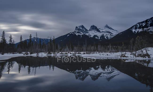 Les Rocheuses canadiennes à jour sombre, les trois sœurs reflètent dans lake (Alberta), Canada, Amérique du Nord — Photo de stock