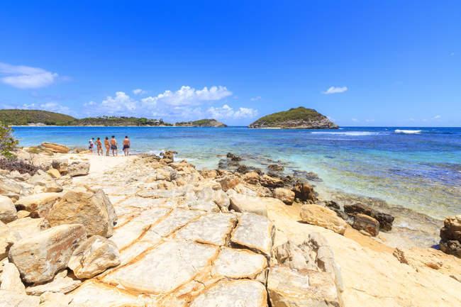 Kristallmeer und felsiger Strand mit Menschen auf dem Hintergrund, Half Moon Bay, Antigua und Barbuda, Leeward Islands, Westindien, Karibik, Mittelamerika — Stockfoto