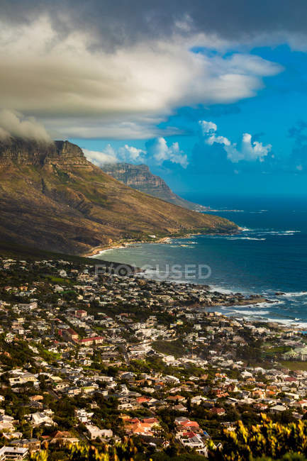 View of Camps Bay with cliffs and coastal buildings under cloudy sky, Cape Town, South Africa, Africa — Stock Photo