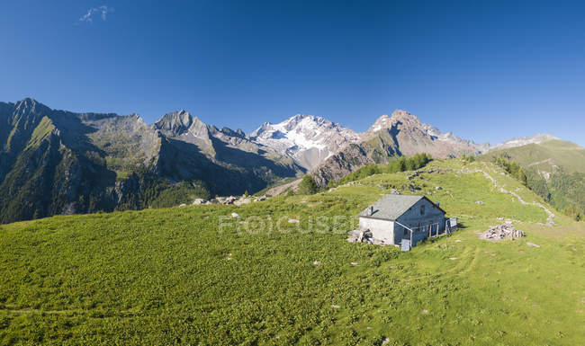 Panoramic view of hut on green meadow in mountains, Scermendone Alp, Sondrio province, Valtellina, Rhaetian Alps, Lombardy, Italy, Europe — Stock Photo