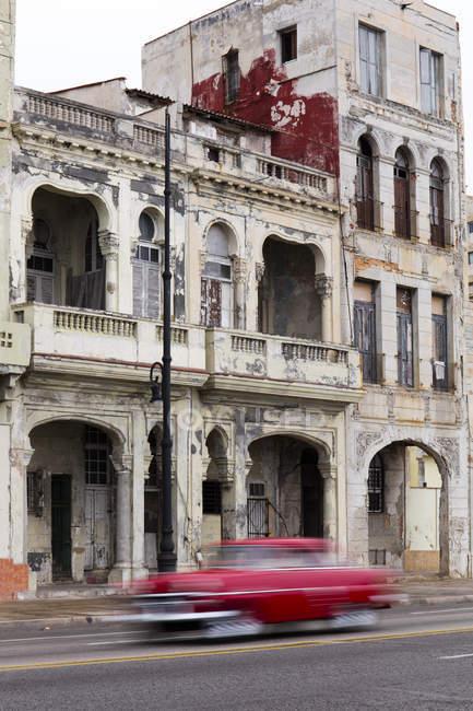 Размыто, Красный ретро автомобиль вождения вдоль Малекон, Гавана, Куба, Вест-Индии, Карибского бассейна, Центральной Америки — стоковое фото